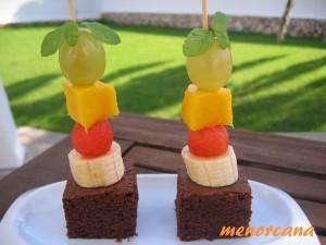 Esta receta la tengo hace mucho tiempo y creo que la saqué de una revista. La original lleva la fruta y las nueces dentro del Brownie… el bizcocho queda muy jugoso!!! Para variar la presentación… he hecho brochetas con porciones de brownie y fruta… uvas, mango, bolas de sandía, plátano… y una hojitas de hierbabuena!!!!!!